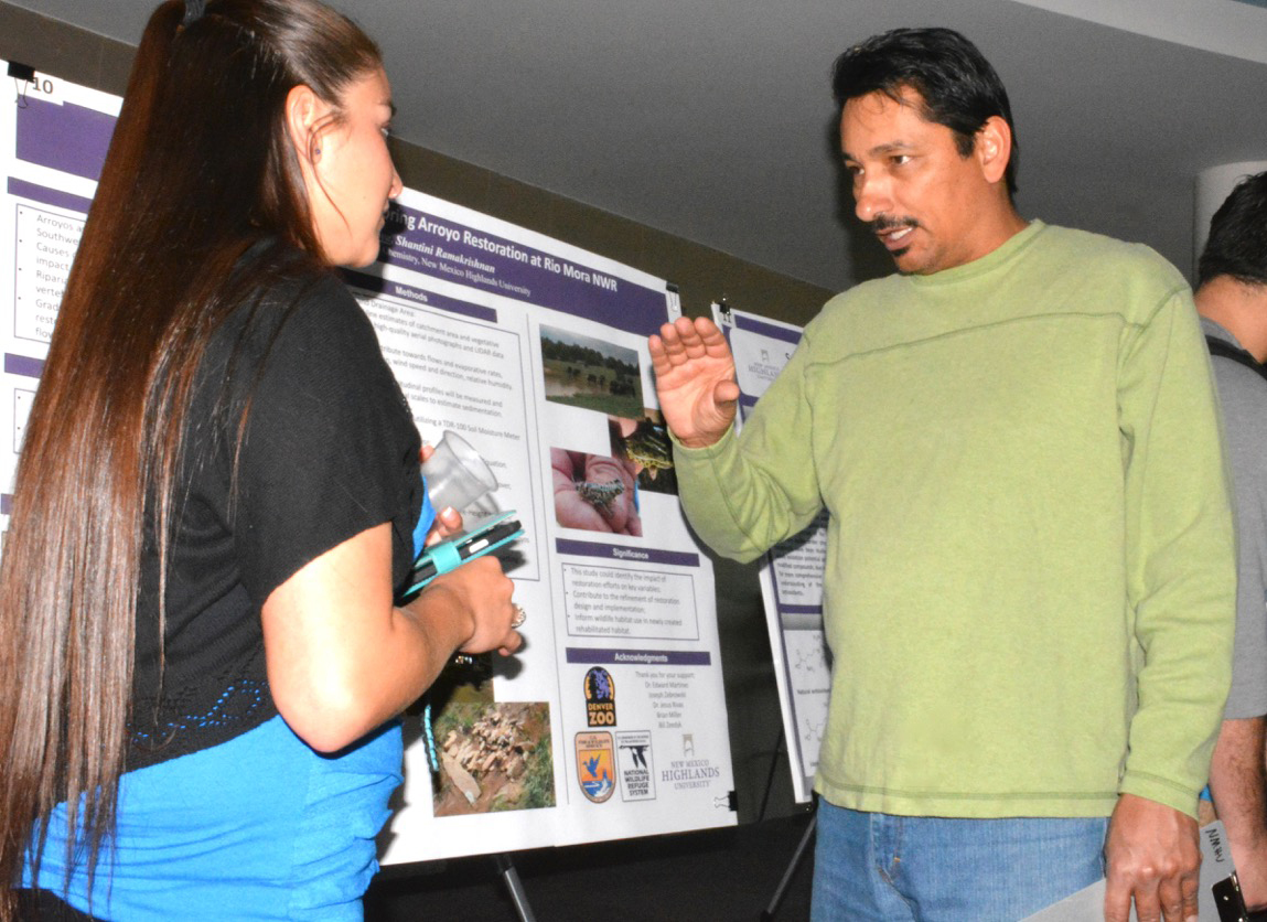 Highlands University natural resources management professor Edward Martínez, right, talks with Eliza Montoya about her research poster at Research Day 2015; photo by Margaret McKinney/Highlands University